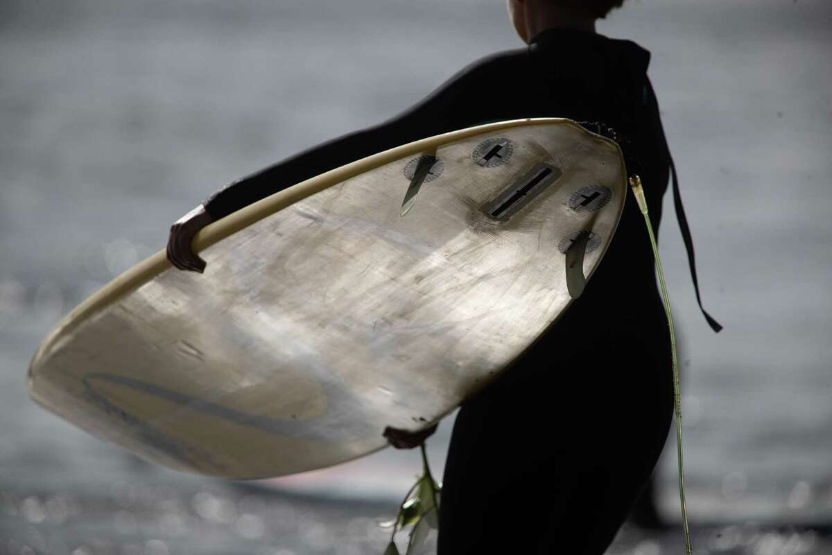 A surfer heads out to form a circle at the opening ceremony for the Mavericks big-wave surf contest on Friday, Oct. 26, 2018, in Half Moon Bay, Calif.