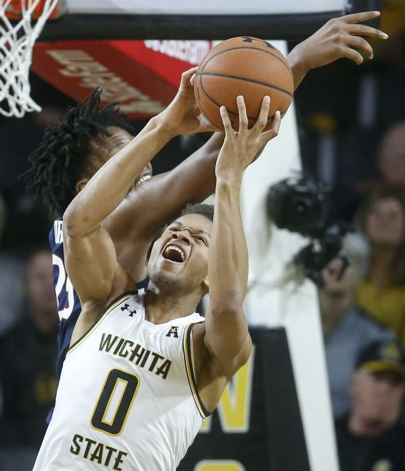 Wichita State's Dexter Dennis fights for a rebound against UConn's Josh Carlton on Thursday night. Photo: Travis Heying / Associated Press / The Wichita Eagle