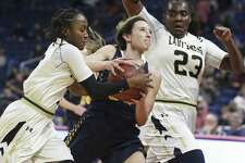 Pirette guard Kyrah Luna is squeezed in the lane at the end of a fastbreak by Telia Jackson, left, and Jordyn Beaty as Poth plays Woodville in the girls 3A state semifinal basketball game at the Alamodome on February 28, 2019.