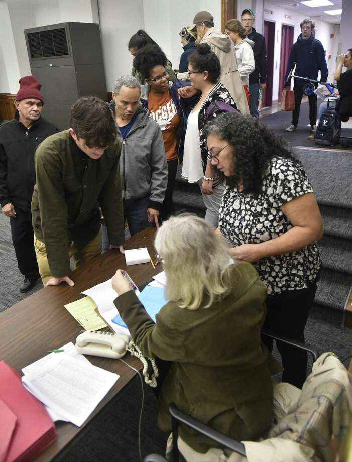 Luz Catarneau, the Ward-17 poll moderator at the Hall of Records in New Haven, right, helps people with Election Day voting issues Nov. 6, 2018. Photo: Peter Hvizdak / Hearst Connecticut Media / New Haven Register