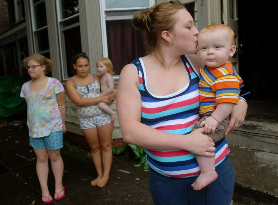 Lindsey Anspach, 21, right, holds her 10-month-old son Ethan Boehm at their home Friday in Troy. Joining them are her sisters Desiree McReynolds, 10, left, and Mercedes Giordano, 11, who holds Anspach's daughter Alyssa, 2. Troy Police Officer Jeff Combs saved Ethan from choking on a staple. (Cindy Schultz / Times Union) Photo: CINDY SCHULTZ / 00009614A