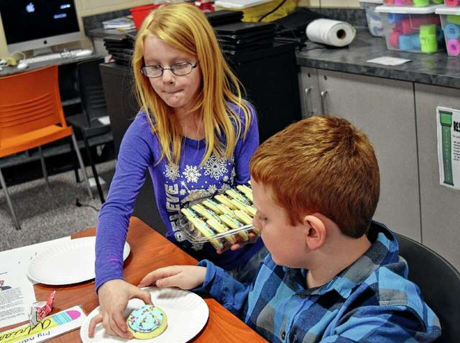 Lillie Ottwell, a fourth grader at Virginia Elementary School, passes out cookies to classmate Coby Masters in honor of her birthday Thursday.
