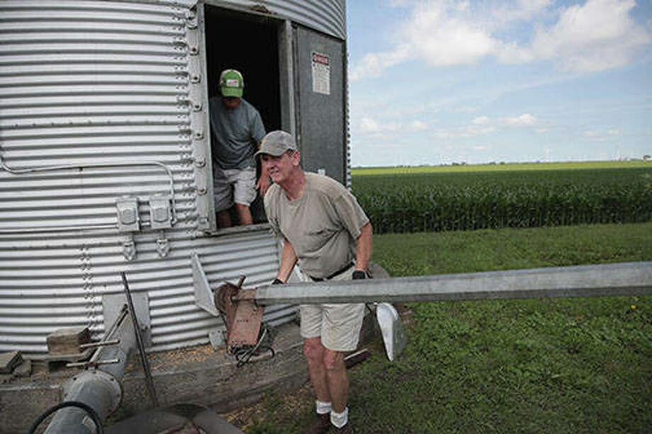 Farmer John Duffy (left) and Roger Murphy load soybeans from a grain bin onto a truck before taking them to a grain elevator in Dwight. Slumping prices for farmers has pushed the delinquency rate for farm loans to the highest point in nine years. Photo: Scott Olson | Getty Images