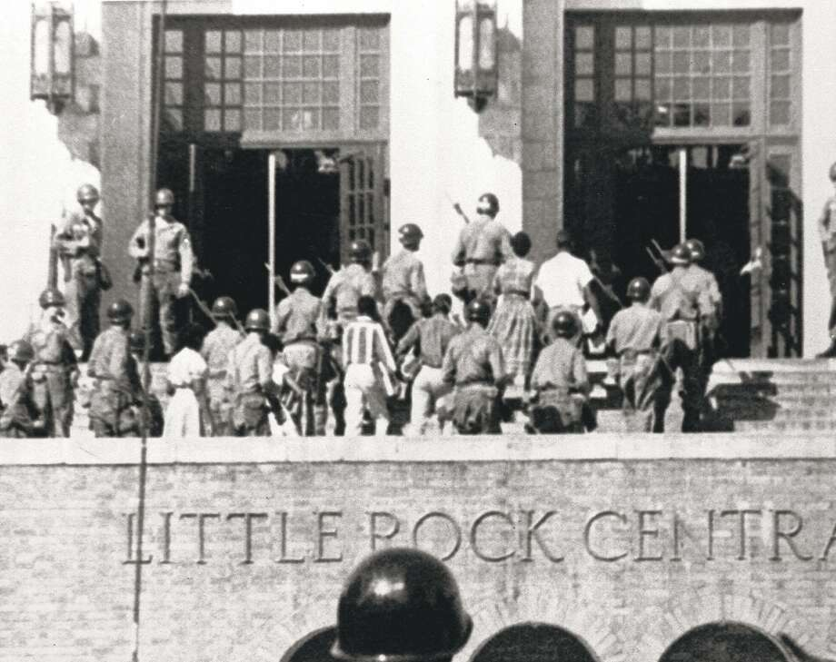 FILE--Troops escort nine black students into Central High School in Little Rock, Ark., Sept. 25, 1957. After then-Gov. Orval E. Faubus posted National Guard troops to block the teens' way, President Eisenhower ordered Army paratroopers to escort them in. It was the first major physical confrontation over states' rights and school desegregation after the landmark 1954 Supreme Court ruling in Brown v. Board of Education of Topeka, Kan., which outlawed deliberate racial segregation in public schools. (AP Photo/File) Photo: AP
