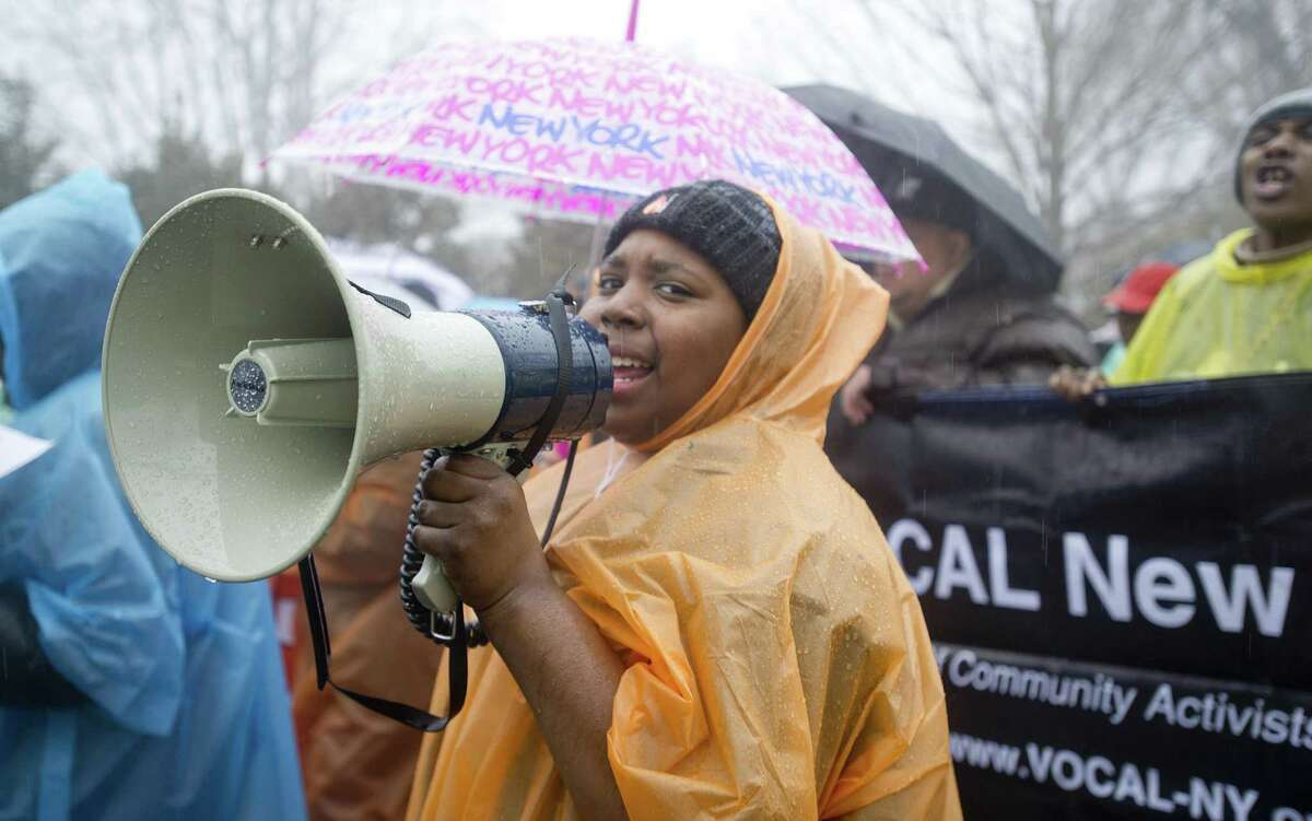 Deavonte Kimble uses a megaphone as she and other marchers move toward Field Point Circle in Greenwich, Conn., on March 14, 2015, to protest hedge fund manager Paul Tudor Jones' funding of Republican politicians. The protestors, marching with the