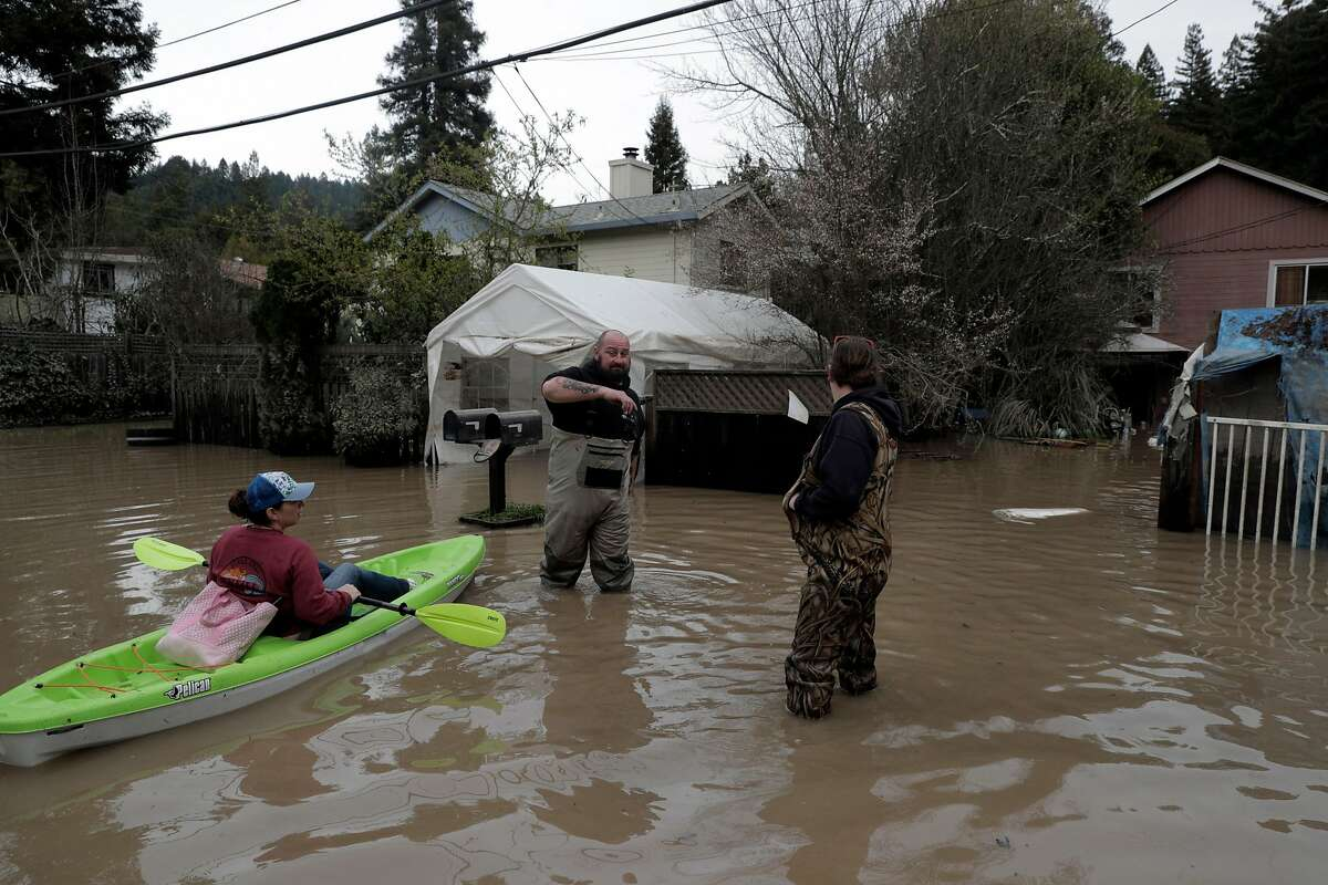 Erin Cardiff (left) talks to her neighbors, Josh Hogg (center) and Teake Bartling (right) near River Road in Forestville in February 2019. The area along the Russian River sustained heavy flooding after an atmospheric river dumped almost 20 inches of rain in two days.