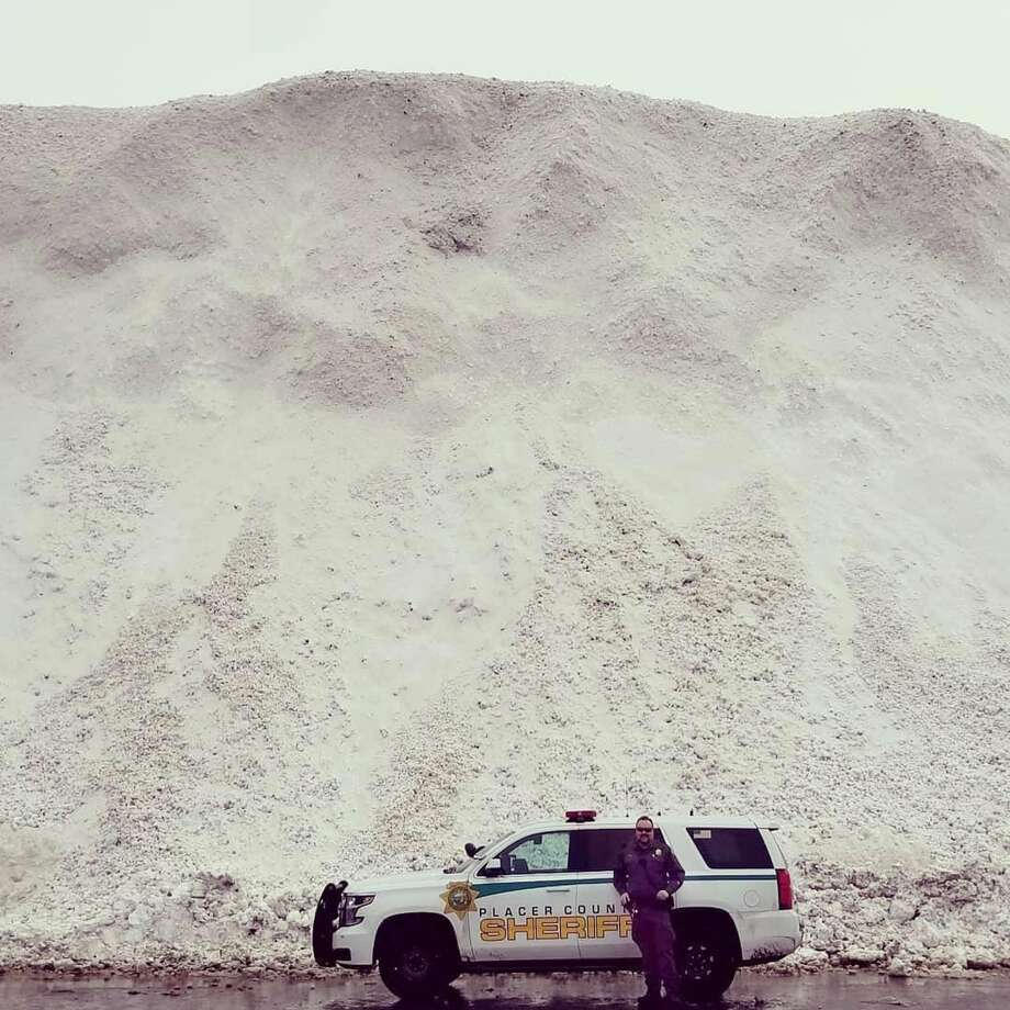 The Placer County Sherriff's Office shared an image showing an officer standing next to the massive snow pile next to a road in North Lake Tahoe on Feb. 28, 2019. Photo: Placer County Sherriff's Office