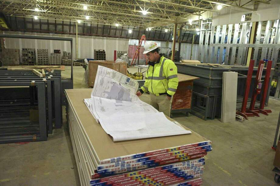 Tim Chan, project manager with O&G Industries, looks at plans for the new agriscience academy at Shepaug Valley School in the new multi-purpose room. Washington, Conn. Wednesday, February 27, 2019. Photo: H John Voorhees III / Hearst Connecticut Media / The News-Times