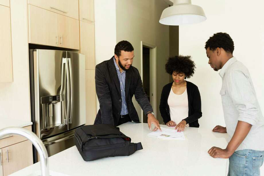 Couple talking to broker in new house Photo: Roberto Westbrook / ©Roberto Westbrook/Blend Images LLC