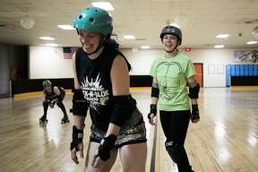 Dawn Sweebe of Sanford, left, laughs with Katie Davis of Bay City, right, after Sweebe hip-checked Davis during a practice for their roller derby team, the Chemical City Derby Girls, on Monday, Feb. 25, 2019 at the Roll-Arena in Midland. (Katy Kildee/kkildee@mdn.net)