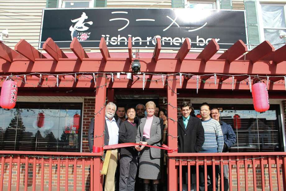CITY'S FIRST: Mayor Nancy R. Rossi, center, cuts the ribbon Feb. 25 with Iishin Ramen Bar chef and co-owner Johnny Chen, second from left, and co-owner Penny Gao, third from left, to mark the ceremonial opening of the city's first ramen restaurant at 291 Captain Thomas Blvd., formerly Savin Rock Roasting Co. Also marking the event are, from left, state Rep. Charles J. Ferraro, R-West Haven; mayoral executive assistant Lou Esposito; Iishin waiter Andy Xu; Gao's mother, Cindy Gao; state Rep. Michael A. DiMassa, D-West Haven; Gao's father, Jackie Gao; and Fred A. Messore, city commissioner of planning and development. The reaturant offers cocktails, appetizers, rice bowls and more. Iishin Ramen Bar is open from noon to 10 p.m. Sunday through Thursday, and from noon to 11 p.m. Friday and Saturday. Photo: Contributed Photo / City Photo - Michael P. Walsh