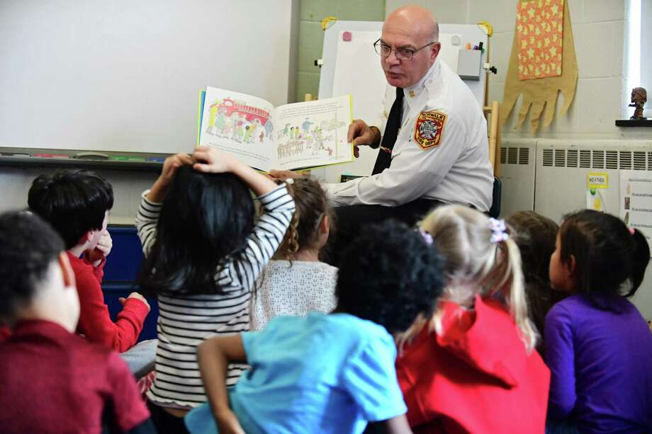 Norwalk Fire Chief Gino Gatto reads Curious George to kindergartners in Abby Peterson's class Friday as students, faculty and staff celebrate Read Across America Day at area schools including Wolfpit Elementary School in Norwalk. Photo: Erik Trautmann / Hearst Connecticut Media / Norwalk Hour