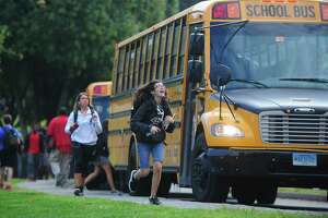 Norwalk High School students catch their First Student buses after school Friday, September 15, 2017, in Norwalk, Conn. Nearly two weeks into the school year, Norwalk Public Schools are still struggling with bus routes, some of which have been consolidated. Buses have been consistently late and overcrowded.
