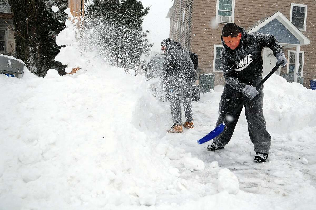 During a nor-easter that is pounding the region, Giovanni Ramos and his friend Curtis Rushing, in back, shovel snow in front of their home on Holly Street in Bridgeport, Conn., on Thursday Jan. 4, 2018.