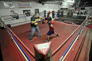 Orlando Montalvo, left, helps Alberto Alamilla practice his hitting while in the ring at Montalvo's Boxing Gym in Stamford, Conn., on Wednesday, Feb. 26, 2014. Orlando is the owner of the gym and is being forced out by an increase in rent in his South End neighborhood.