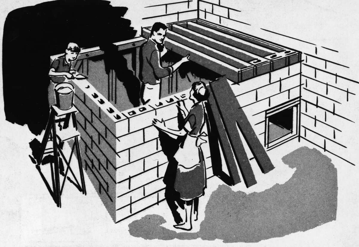 Illustration of a family building a bomb fallout shelter together, using sand-filled concrete blocks for roof shielding, from a U.S. Department of Defense publication, 1961.