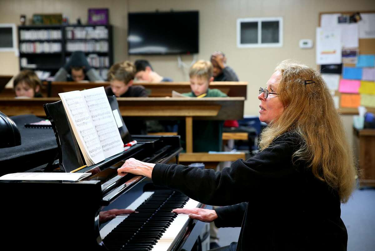 Marcia Roy, artistic program director and founder, plays the piano during class at Pacific Boyschoir Academy in Oakland, Calif., on Wednesday, February 27, 2019. The school received a donation of four major Asian pieces of art, which appraisers valued at $2.8 million. They started spending the anticipated windfall only to find out the paintings were duplicates. So now the school is facing a mountain of debt and imminent closure unless they can repay the loans.