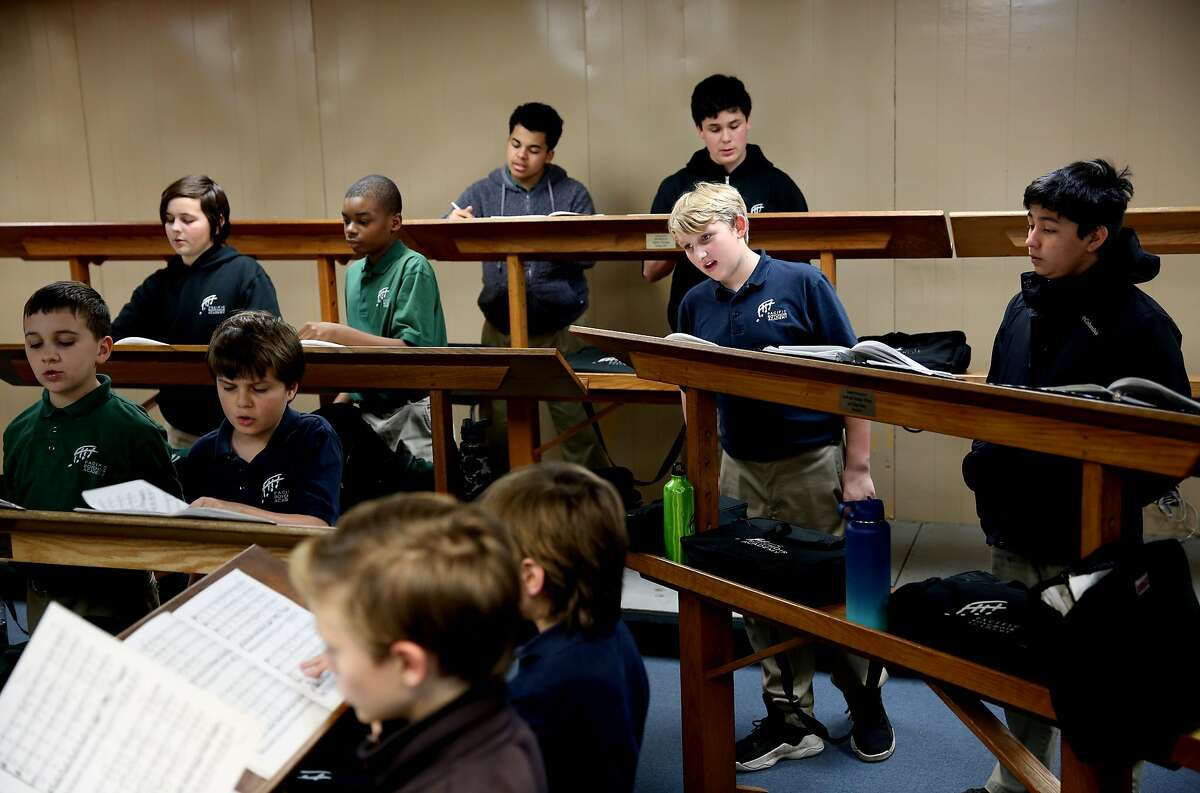 Students sing during class at Pacific Boyschoir Academy in Oakland, Calif., on Wednesday, February 27, 2019. The school received a donation of four major Asian pieces of art, which appraisers valued at $2.8 million. They started spending the anticipated windfall only to find out the paintings were duplicates. So now the school is facing a mountain of debt and imminent closure unless they can repay the loans.