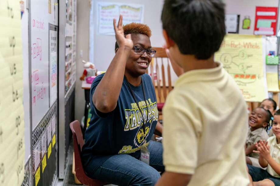 Angeliner Avington, teacher at Thompson Elementary School in Spring ISD, gives a student a high five during class. Photo: Courtesy Of Spring ISD