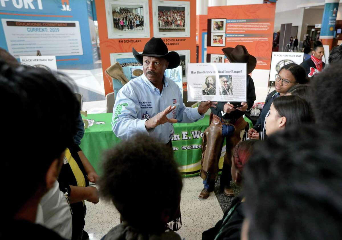 Larry Callies, center, a co-founder of the Black Cowboy Museum in Rosenberg, Texas, tells a group of students from Worthing High School about the lone ranger on Black Heritage Day at the Houston Livestock Show and Rodeo Friday, March 1, 2019, in Houston.