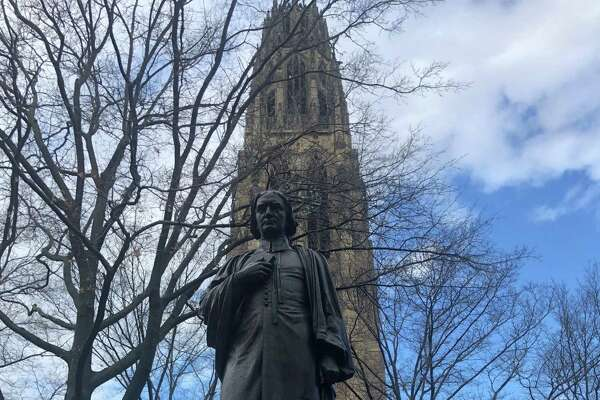 A statue of the Rev. Abraham Pierson in the Old Campus quad at Yale University in New Haven, Connecticut. Pierson, 1646-1707, was the first rector (1701-07) and one of the founders of the Collegiate School, which later became Yale University. Harkness Tower is behind Pierson.