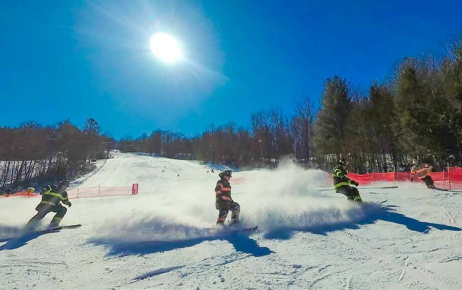 Firefighters race down the hill at Mohawk Mountain Ski Area in Cornwall during the 2018 Firefighter Race. The event, which benefits the Connecticut Burn Center at Bridgeport Hospital, will be held Sunday, March 10. Photo: Photo By Tom Mitchell /