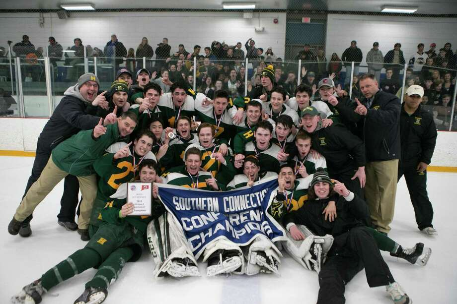 Members of the Hamden boys hockey team celebrate after winning the SCC Division I championship on Friday. Photo: John Vanacore / For Hearst Connecticut Media / (C)John H.Vanacore
