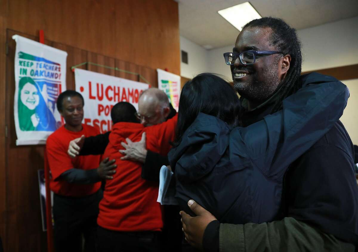 Keith Brown (right), president, Oakland Education Association, receives a hug from Mary Nicely, Senior Policy Advisor to the CA State Superintendent of Public Instruction, following a press conference that announced a tentative settlement has been reached in the Oakland teacher's strike at Taylor Memorial United Methodist in Oakland, Calif., on Friday, March 1, 2019.