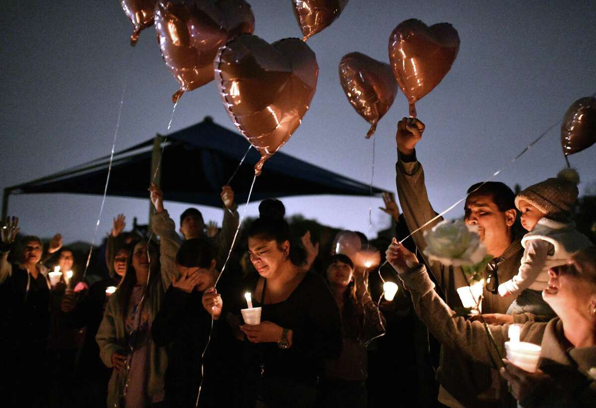 Sally De Leon, middle, older sister of Kaitlin Leonor Castilleja, 18, who was fatally stabbed, releases a balloon during a vigil Friday night, March 1, 2019, along with other family members. .