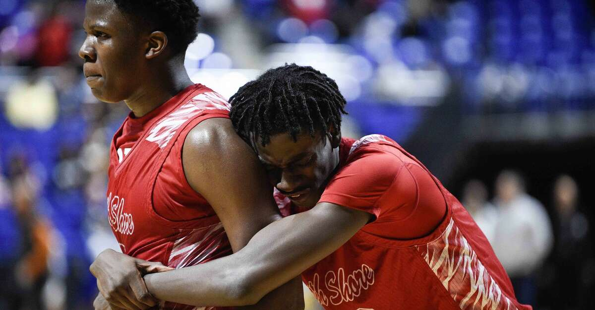 North Shore's Randy Woodard, right, hugs teammate Keiman Capers after the team's overtime win over Elkins in a 6A regional semifinal high school basketball game, Friday, March 1, 2019, in Cypress, TX.