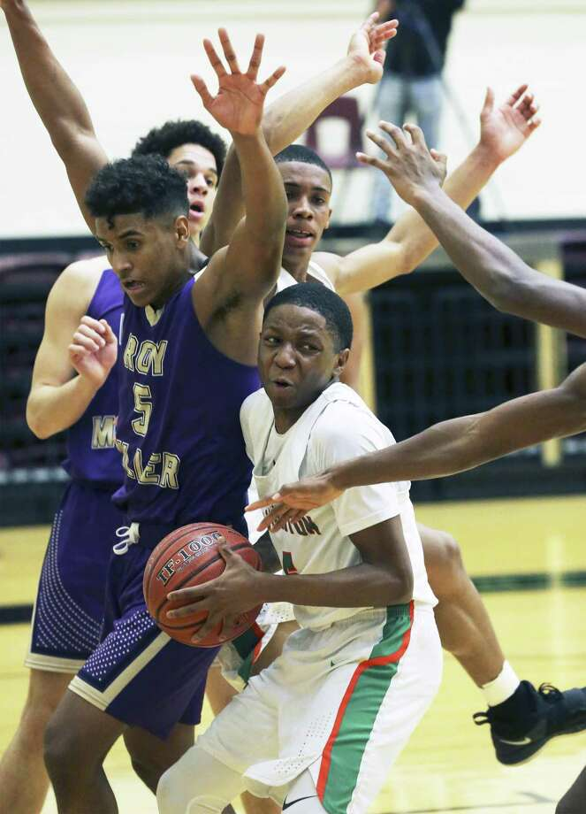 Hurricane guard Tyrese Wolford gets a grasp on a rebound but is surrounded by defenders as Sam Houston plays Corpus Christi Miller in Region IV-5A boys basketball playoffs at Little ton Gym on March 1, 2019. Photo: Tom Reel, Staff / Staff Photographer / 2019 SAN ANTONIO EXPRESS-NEWS