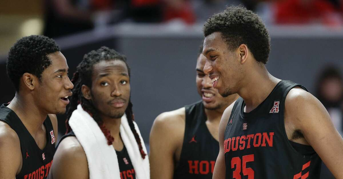 Houston forward Fabian White Jr. (35) clasps hands with teammate Brison Gresham after White fouled out during the second half of an NCAA college basketball game, Saturday, Feb. 23, 2019, in Houston. Houston won the game 71-59.