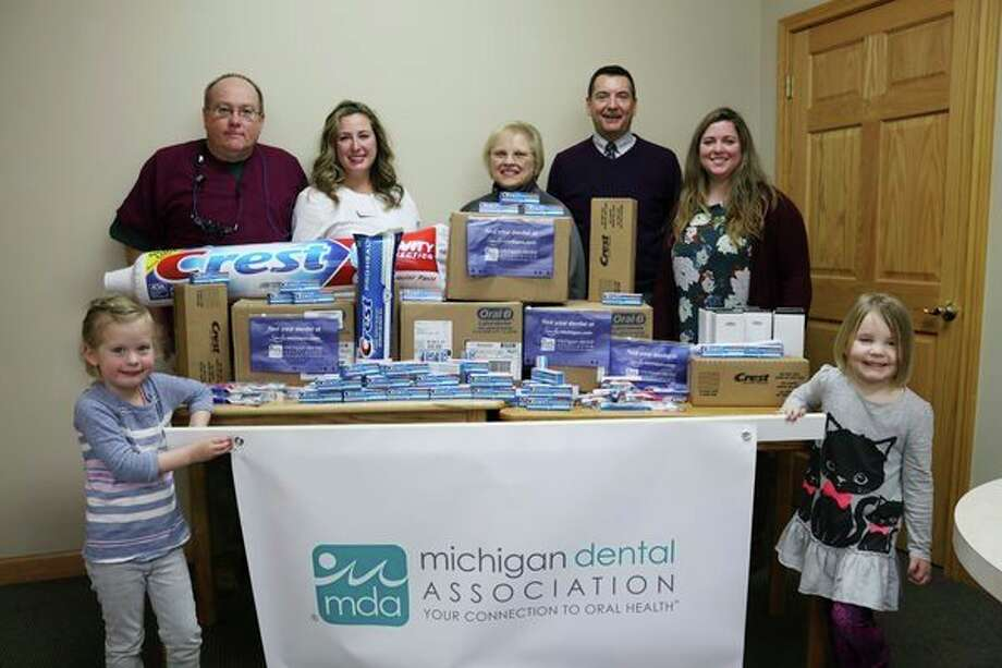 Dr. Chris Jones (rear left) poses among others with thousands of toothbrushes and tubes of toothpaste to be handed out to area kids. (From left) Mila Konkus, 4; Chris Jones, doctor of dental surgery; Camille Secor, doctor of medicine in dentistry; Cynthia Young of Midland Public Schools; Larry Eischer from Crest/OralB; Jane Harrington from Jones & Secor Family Dentistry and Cate Tierney, 4. (photo provided)