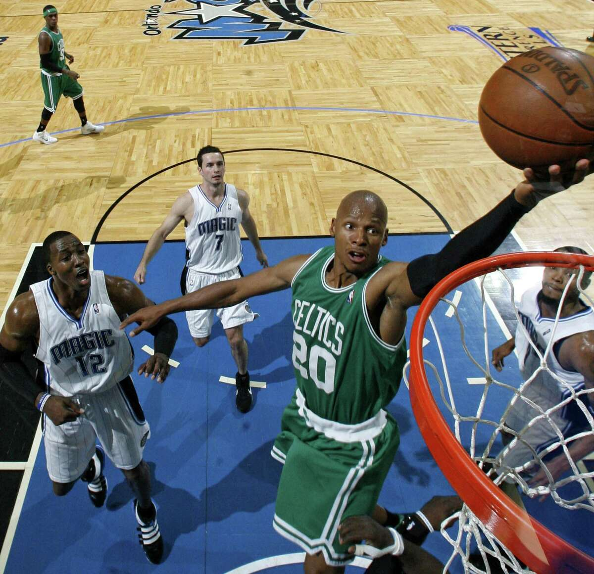 Ray Allen goes up for a shot past Orlando Magic's Dwight Howard, J.J. Redick, and Rashard Lewis during the first half in Game 1 of the NBA Eastern Conference finals on May 16, 2010.