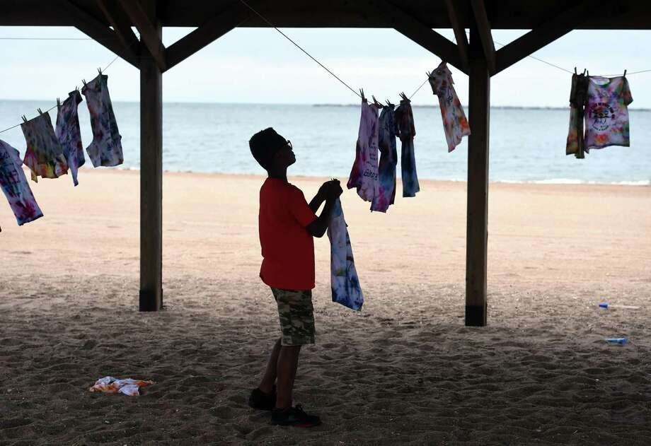 A child hangs a shirt he tie-dyed to dry at a Lead Awareness Picnic at Lighthouse Point Park in New Haven. Photo: Arnold Gold / Hearst Connecticut Media File Photo
