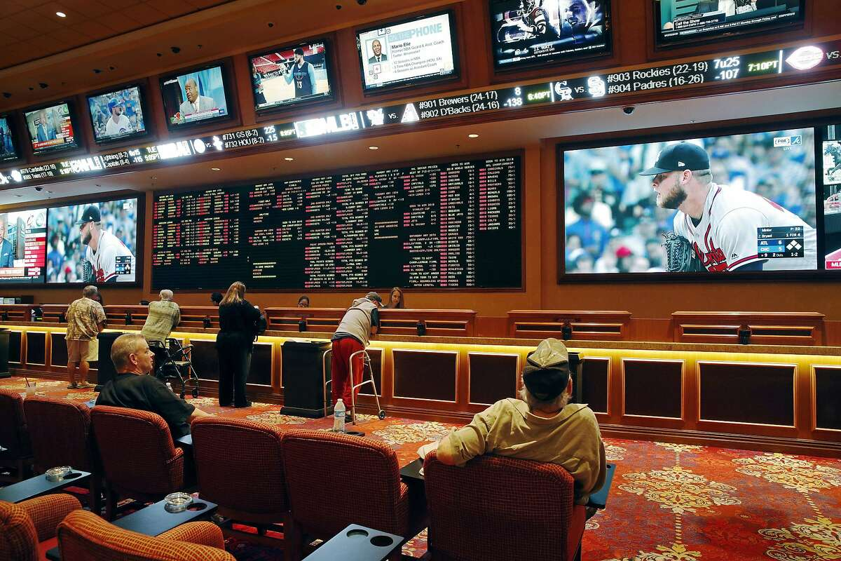 FILE - In this Monday, May 14, 2018, file photo, people make bets in the sports book at the South Point hotel and casino in Las Vegas. Nevada regulators have rejected a request from Major League Baseball to ban betting on spring training games. The Nevada Gaming Control Board says the state has the proper controls in place to minimize the league's integrity concerns. (AP Photo/John Locher, File)