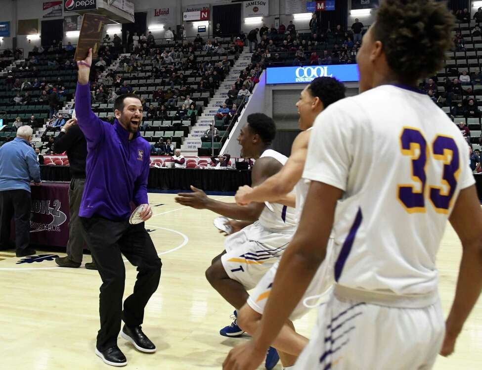 Troy boys basketball head coach Greg Davis holds the Section II Champions plaque above his head as his players run to him following their Class A sectional final against Gloversville at Cool Insuring Arena in Glens Falls, N.Y. on Saturday, Mar. 2, 2019. (Jenn March, Special to the Times Union )