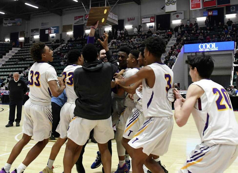 Troy boys basketball players swarm their coach, Greg Davis following their Class A sectional final against Gloversville at Cool Insuring Arena in Glens Falls, N.Y. on Saturday, Mar. 2, 2019. (Jenn March, Special to the Times Union )
