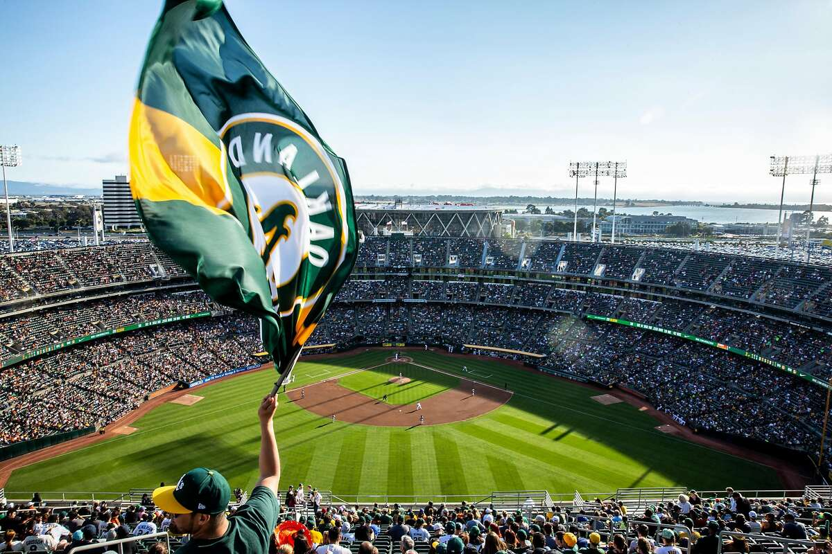 Juan Contreras of Stockton waves an Oakland A's flag near the top of Oakland Coliseum's Mount Davis during an MLB game between the A's and the San Francisco Giants on Saturday, July 21, 2018, in Oakland, Calif. For the first time in 13 years, the A�s opened Mount Davis, the tallest deck in the Oakland Coliseum.