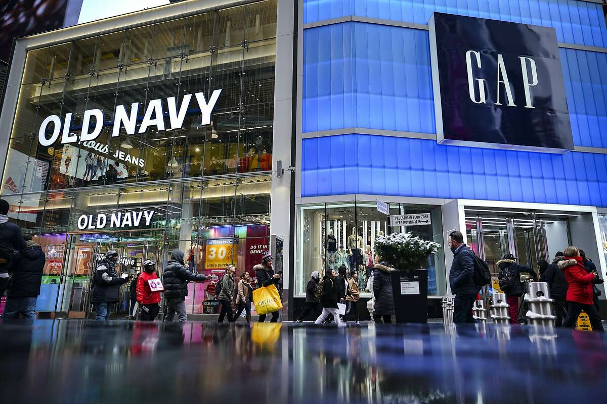 Pedestrians walk past Old Navy and GAP stores in Times Square, March 1, 2019 in New York City. On Thursday, Gap Inc. announced plans to separate into two publicly traded companies, spinning off Old Navy into a separate firm as it closes about 230 Gap stores over the next two years. According to Gap Inc., Old Navy will become its own company, and the other company, which has not been named yet, will consist of the Gap brand, Athleta, Banana Republic, Intermix and Hill City.