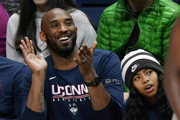 Kobe Bryant and his daughter Gianna watch the first half of an NCAA college basketball game between Connecticut and Houston, Saturday, March 2, 2019, in Storrs.