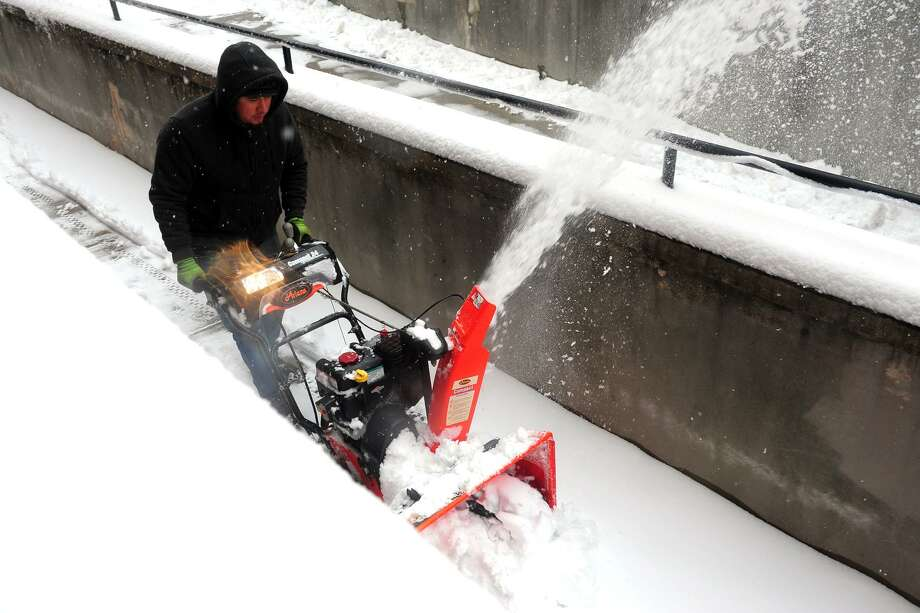 Eddie Terron, of Stamford, uses a snowblower Saturday morning in Bridgeport. Photo: Ned Gerard / Hearst Connecticut Media / Connecticut Post