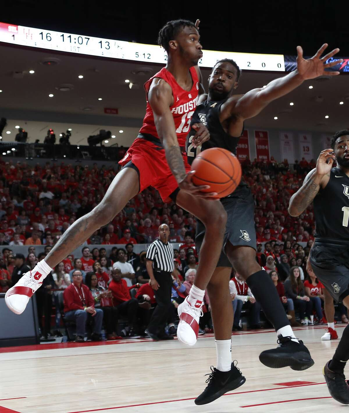 Houston guard Dejon Jarreau (13) flies past Central Florida forward Chad Brown (21) to pass the ball in the lane during the first half on a NCAA basketball game at Fertitta Center on Saturday, March 2, 2019, in Houston.