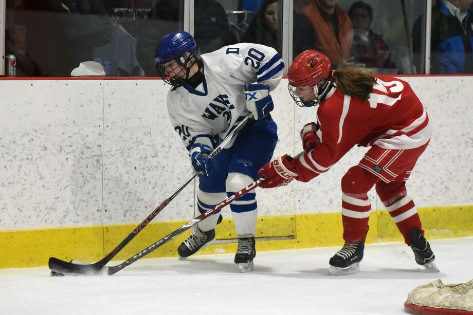 Darien's Nelle Kniffin (20) and Greenwich's Kate Piotrzkowski (15) battle along the boards during a state quarterfinal game at the Darien Ice House on Saturday. Photo: Dave Stewart / Hearst Connecticut Media / Hearst Connecticut Media