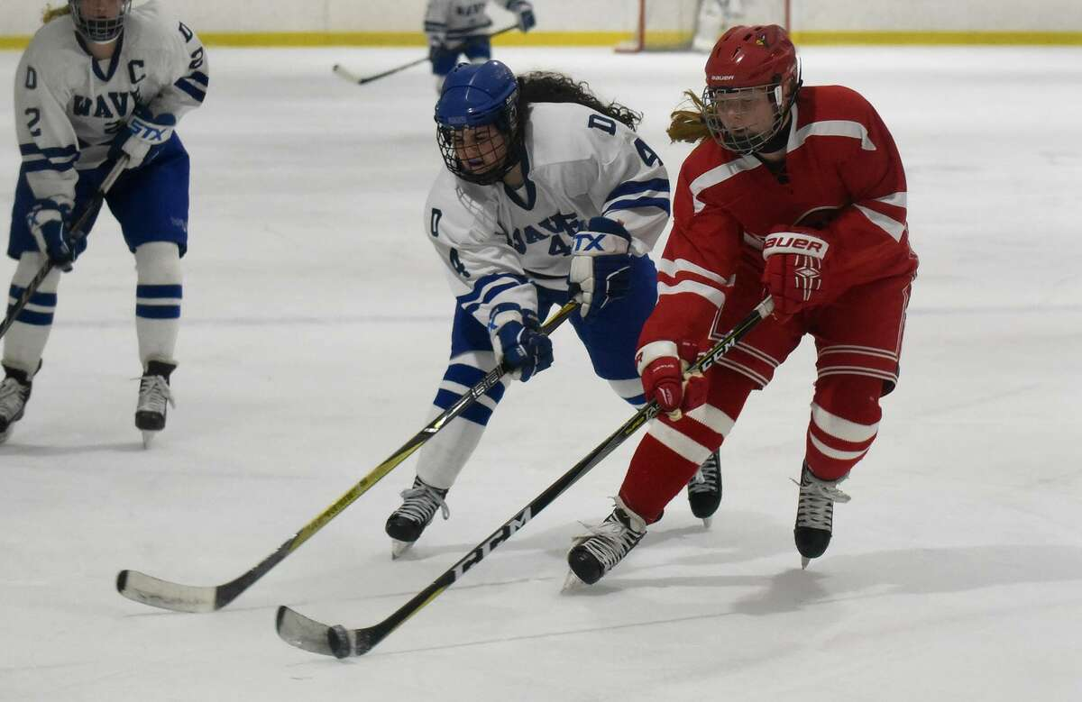 Greenwich's Sydney Orszulak (15) gets to the puck as Darien's Olivia Toscano (4) pursues during a state quarterfinal game at the Darien Ice House on Saturday.
