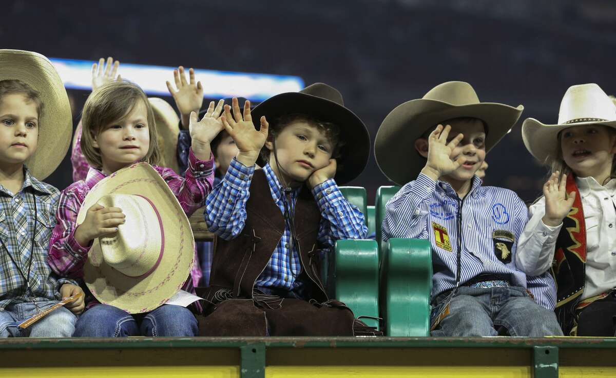 A child waves his hand slowly at the audience during grand entry of the Houston Livestock Show and Rodeo Super Series II Round 3 at NRG Stadium on Saturday, March 2, 2019, in Houston.