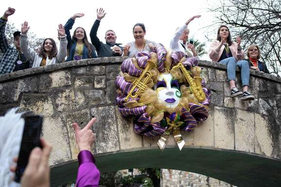 Revelers wave for beads to be thrown during the Bud Light Mardi Gras River Parade and Festival on the San Antonio River Walk, Saturday, March 2, 2019.
