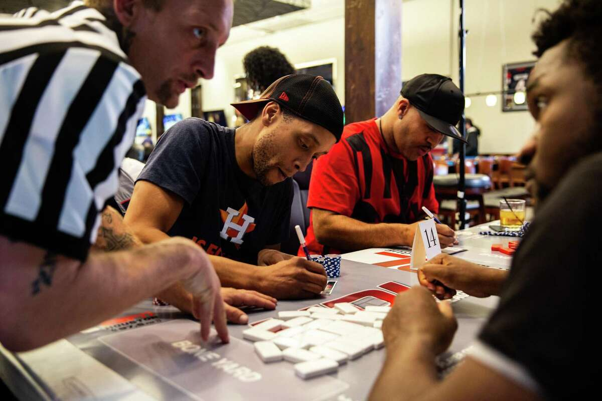 Charles Dow, 37, fills out a match card after winning the round against his opponent at the Houston Prime Classic Domino Tournament on March 02, 2019.