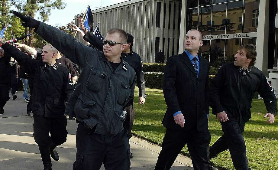 FILE-In this Saturday, Nov. 5, 2011 file photo, Jeff Schoep, second right in business suit, commander of the National Socialist Movement, leave under police protection after a rally against illegal immigration in Pomona, Calif. Photo: Thomas R. Cordova, Associated Press