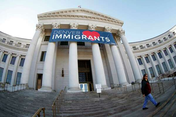 "FILE - In this Feb. 26, 2018 file photo, a banner to welcome immigrants is shown through a fisheye lens over the main entrance to the Denver City and County Building. The U.S. Justice Department told The Associated Press at the end of February 2019 that 28 jurisdictions, including Denver, that were targeted in 2017 over what it considered ""sanctuary"" policies have been cleared for law enforcement grant funding. (AP Photo/David Zalubowski, File)"